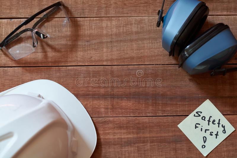 Safety first note one yellow piece of paper stuck on wooden background with full set of personal protective equipment: helmet, saf. Et glasses and ear protection stock images