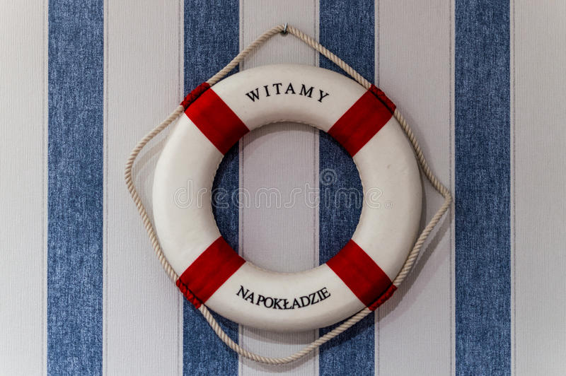 Safety first. Red lifebuoy with welcome aboard hanging on wall with blue white stripes.  royalty free stock images