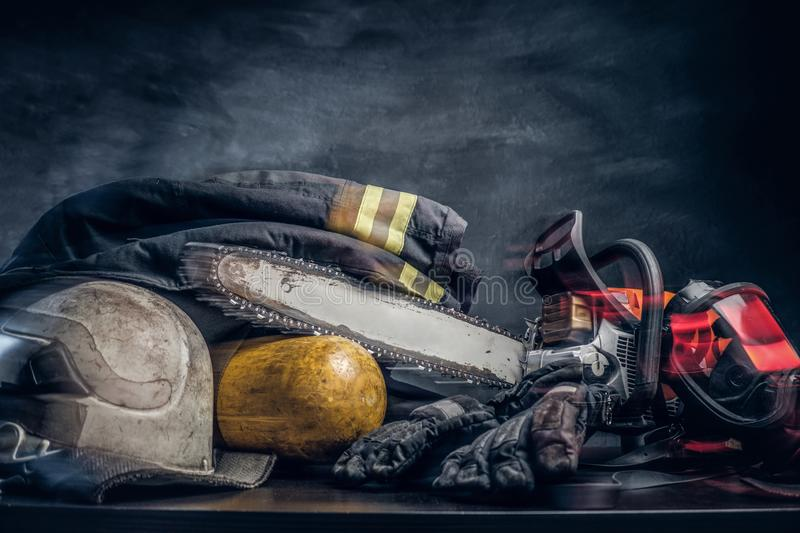 Safety gear, oxygen balon and chainsaw on the table. Safety gear, jacket, oxygen cylinder and chainsaw on the table. There are dark background. Photo has a blur royalty free stock photos