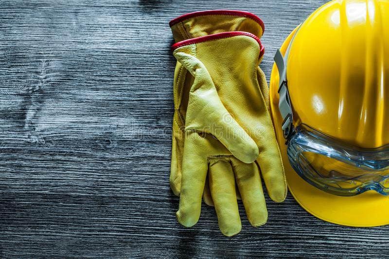 Safety glasses leather gloves hard hat on vintage wooden board royalty free stock photo