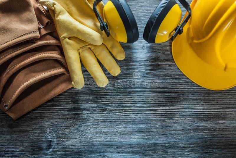 Safety gloves building helmet earmuffs tool belt on wooden board royalty free stock photo