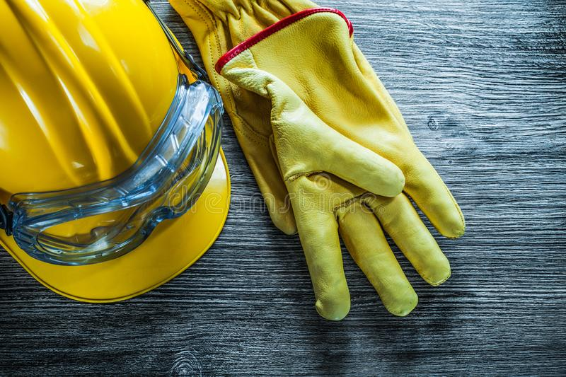 Safety gloves hard hat goggles on vintage wooden board royalty free stock images