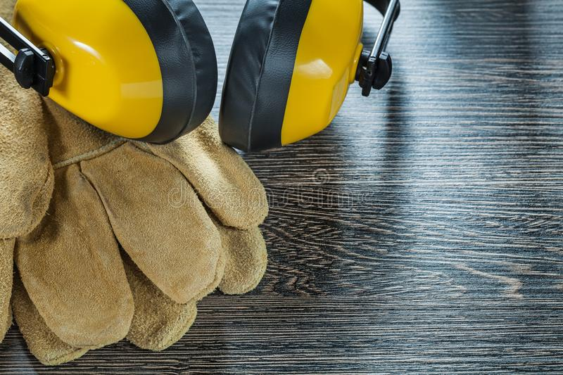 Safety gloves noise reduction ear muffs on black board.  stock image