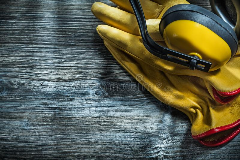 Safety gloves noise reduction earmuffs on wooden board.  stock photos