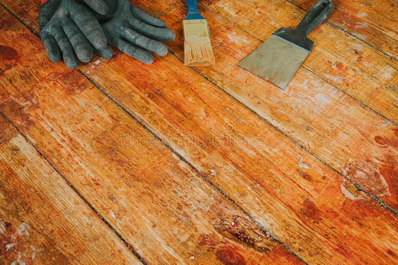Safety gloves with paint brush and scrape tool placed on old wooden floor royalty free stock image