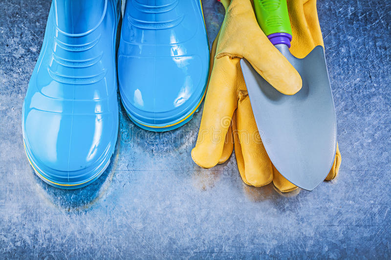Safety gum boots working gloves hand trowel on metallic backgrou. Nd gardening concept royalty free stock images