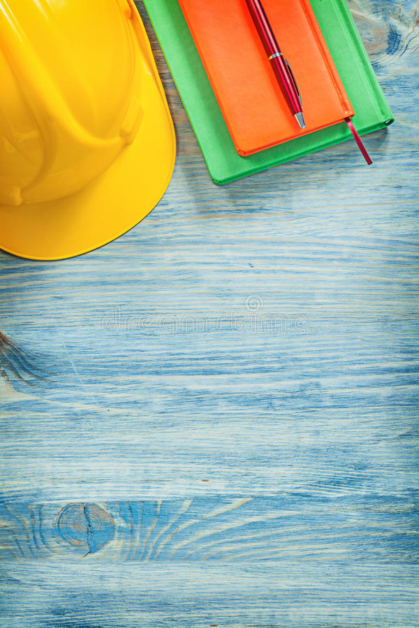 Safety hard hat notepads ball-point pen on wooden board construc. Tion concept royalty free stock images