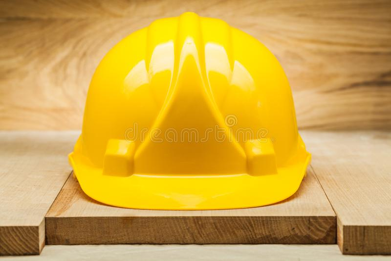 Safety headwear. yellow construction helmet on wood background royalty free stock photography