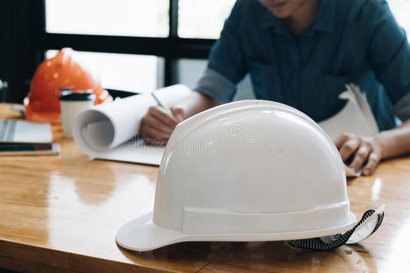 Safety helm with Yong architect man working with blueprints, yon royalty free stock photo