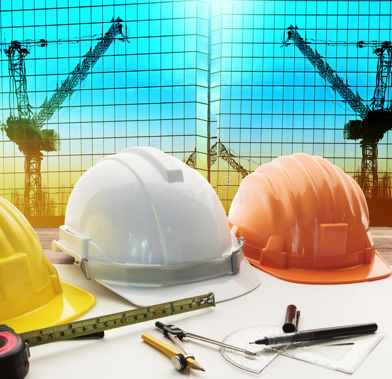 Safety helmet on architect ,engineer working table with modern b stock images