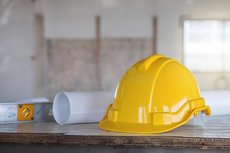 The safety helmet and the blueprint on table at construction site stock images