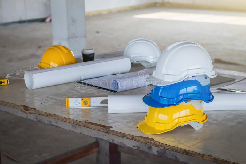 The safety helmet and the blueprint on table at construction site stock photos
