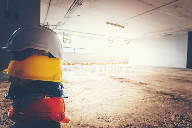 Safety helmet, white, yellow, blue and orange, placed on the cement floor in the construction site.  stock image