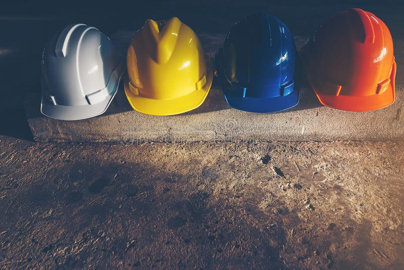 Safety helmet, white, yellow, blue and orange, placed on the cement floor in the construction site.  stock photos