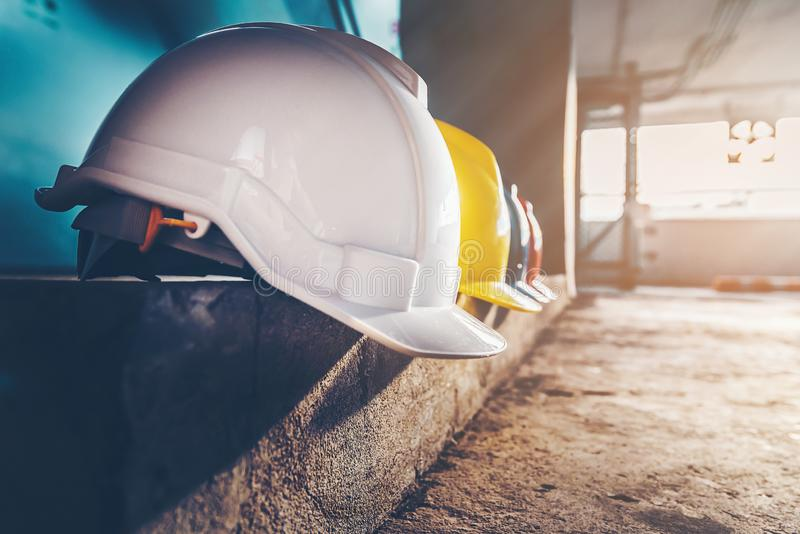 Safety helmet, white, yellow, blue and orange, placed on the cement floor in the construction site.  royalty free stock image