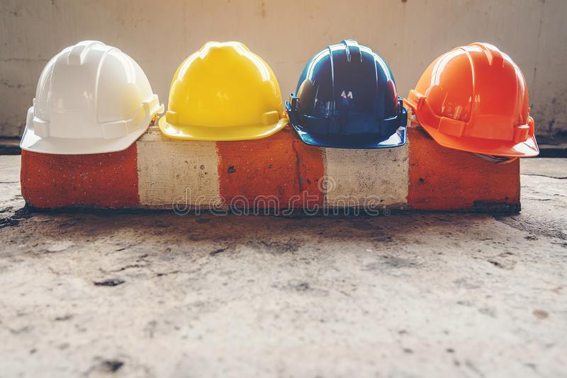 Safety helmet, white, yellow, blue and orange, placed on the cement floor in the construction site.  royalty free stock photography