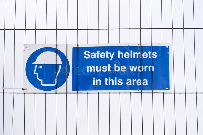 Safety helmets hard hats must be worn sign at construction site stock photography