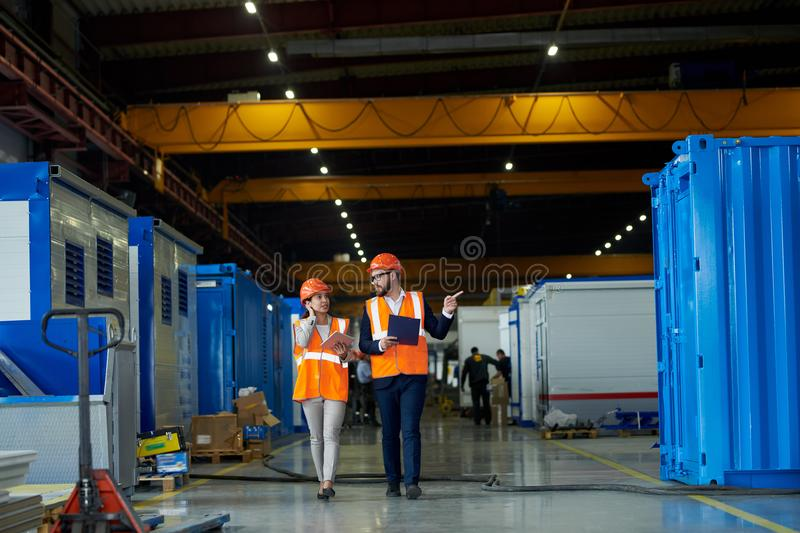 Safety Inspection at Factory. Full length portrait of bearded businessman wearing hardhat talking to female factory worker while discussing production in stock photos