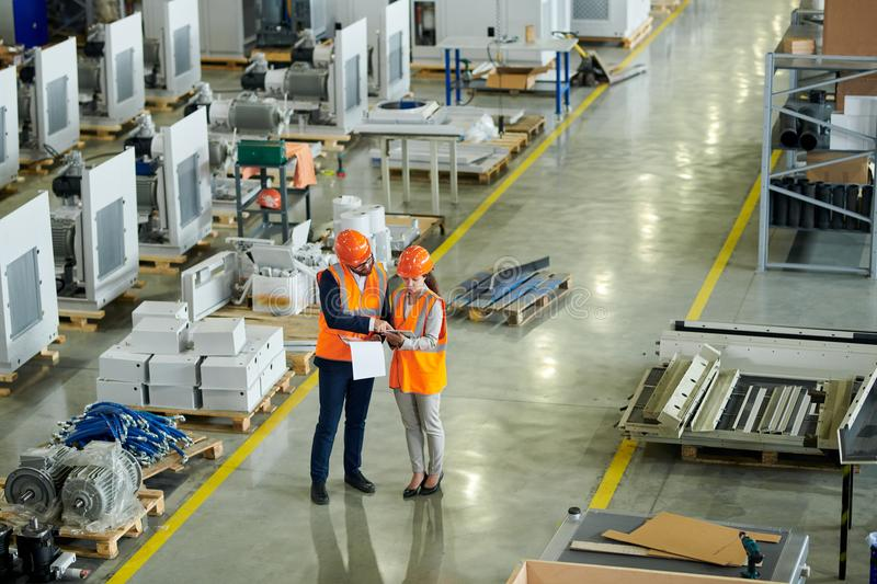 Safety Inspection at Plant. High angle full length portrait of bearded businessman wearing hardhat inspecting production workshop accompanied by female factory royalty free stock photo