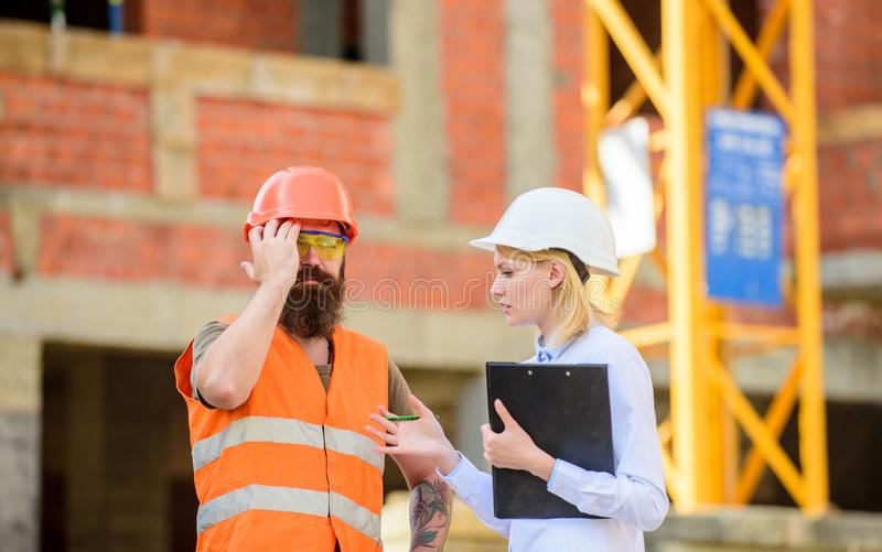 Safety inspector concept. Inspector and bearded brutal builder discuss construction progress. Construction project stock image