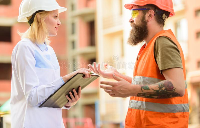 Safety inspector concept. Woman inspector and bearded brutal builder discuss construction progress. Construction site stock images