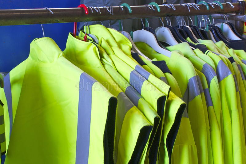 Safety Jackets on hangers stock images