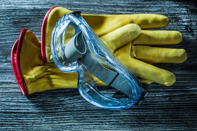 Safety leather gloves glasses on wooden board royalty free stock images