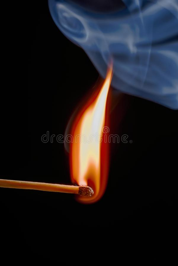 Safety match on black background with flaming head. Vertical photo of match stick. The safety match has flaming hot head but the body is still fine. Nice curly stock image