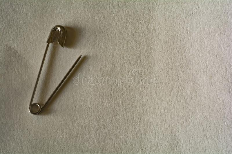 Safety pin on a white paper background stock image