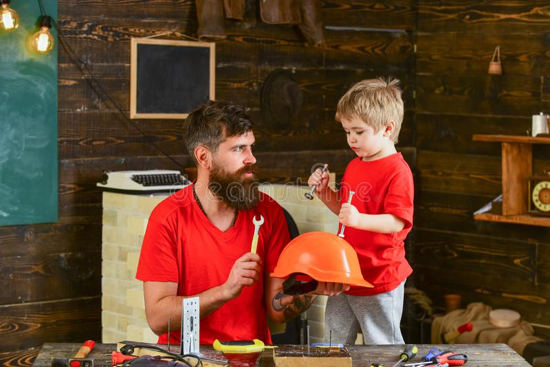 Safety and protection concept. Father, parent with beard holds helmet teaching son safety in school workshop. Boy, child stock photo