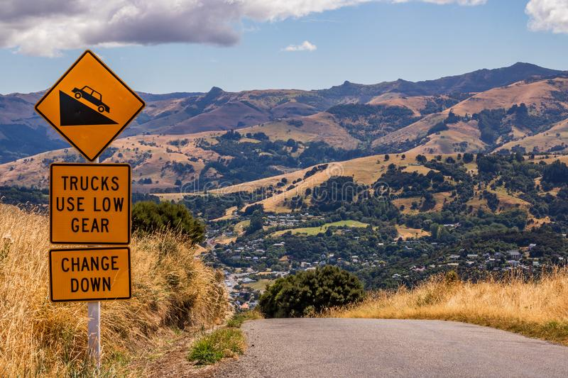 Safety road sign to tell trucks and cars to use low gear before steep downhill road royalty free stock photography