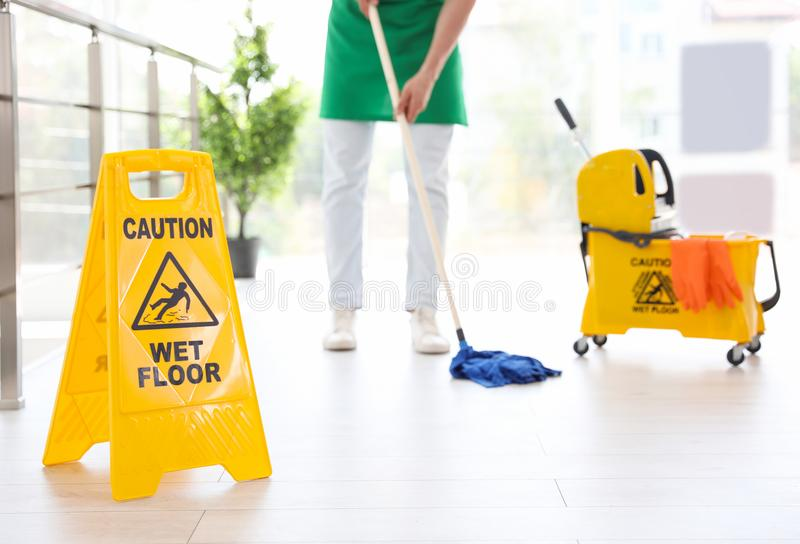 Safety sign with words `CAUTION WET FLOOR` and young man on background stock image