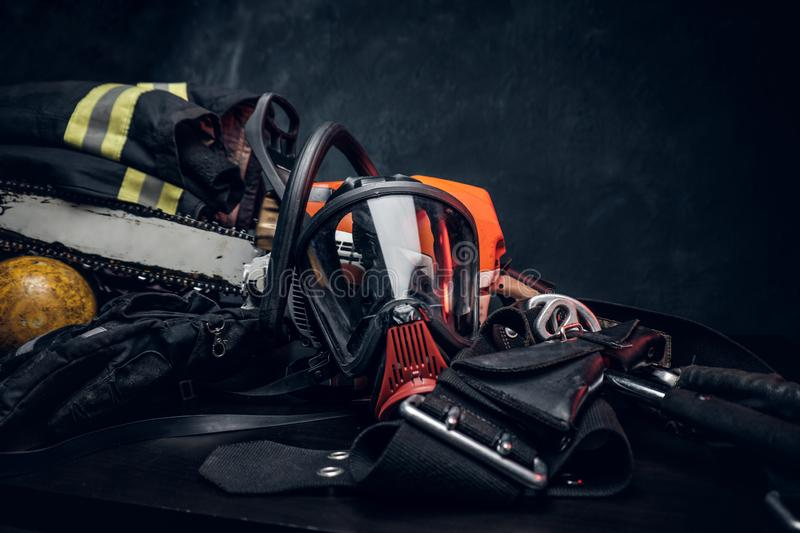 Safety unform on the table with respirator and chainsaw. Safety unform on the table -  jacket and gloves with oxygen cylinder, respirator and chainsaw. There stock images