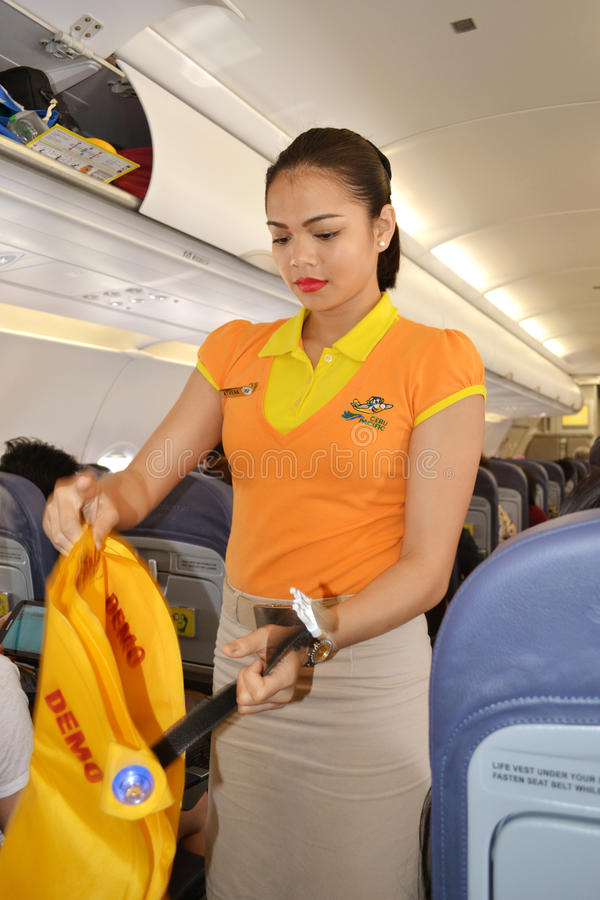 Safety vest. DAVAO, PHILIPPINES - APRIL 19, 2015: Cebu Pacific flight attendant demonstrating safety measures for the passengers. Safety demonstration is a must stock photo