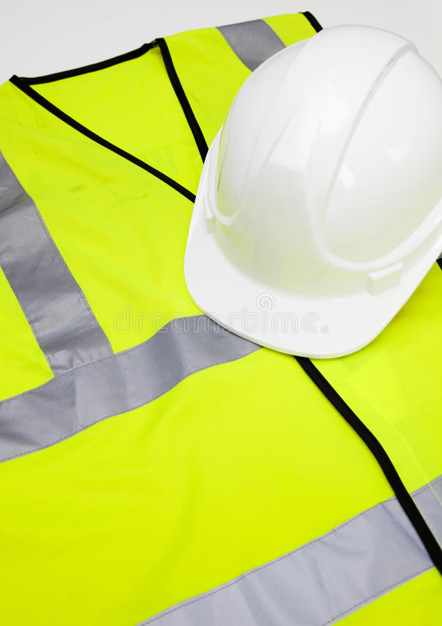 Safety vest and hard hat against white background stock image