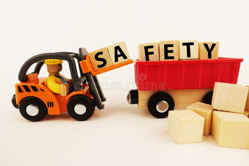Safety at work concept with orange forklift with wooden blocks on white background stock photo