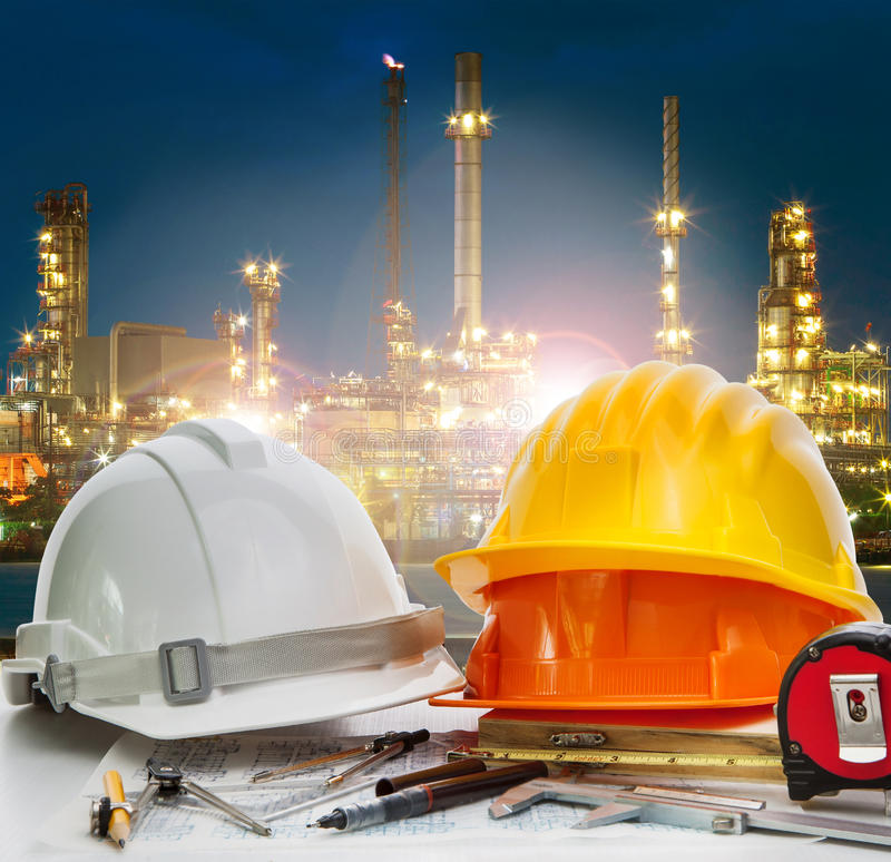 safey helmet on engineer working table agaisnt beautiful lighting of oil refinery in petroleum petrochemical plant use for energy stock photography