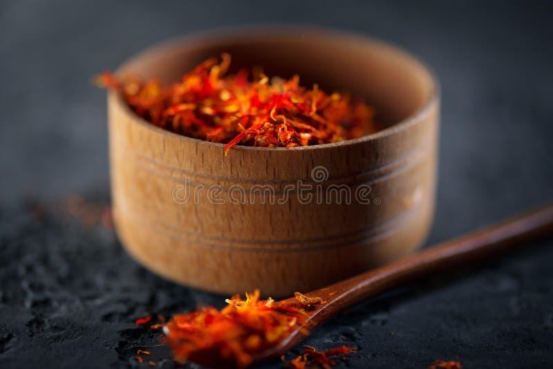 Saffraan Indische kruiden in houten kom op zwarte steenlijst Kruid en kruiden op leiachtergrond cooking royalty-vrije stock afbeelding