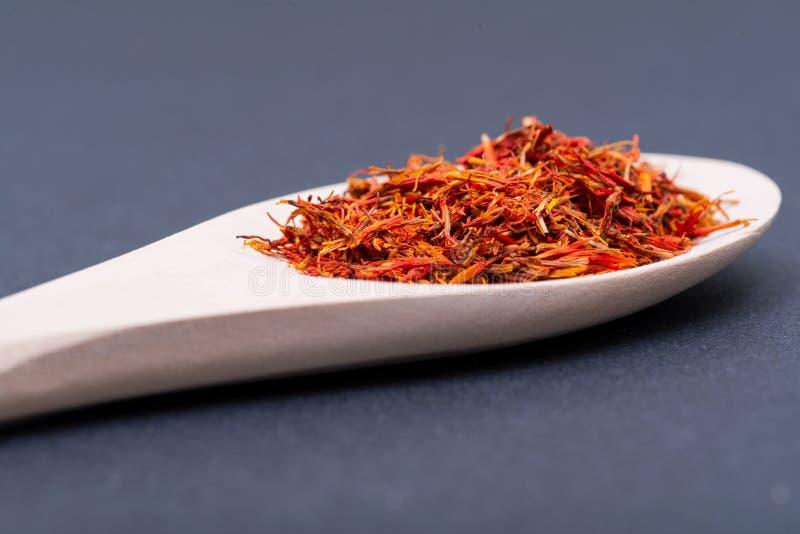 Saffraankruid van de Sativus bloem van Krokus, die algemeen als de ?saffraankrokus ?wordt bekend, in houten lepel op dark stock afbeelding