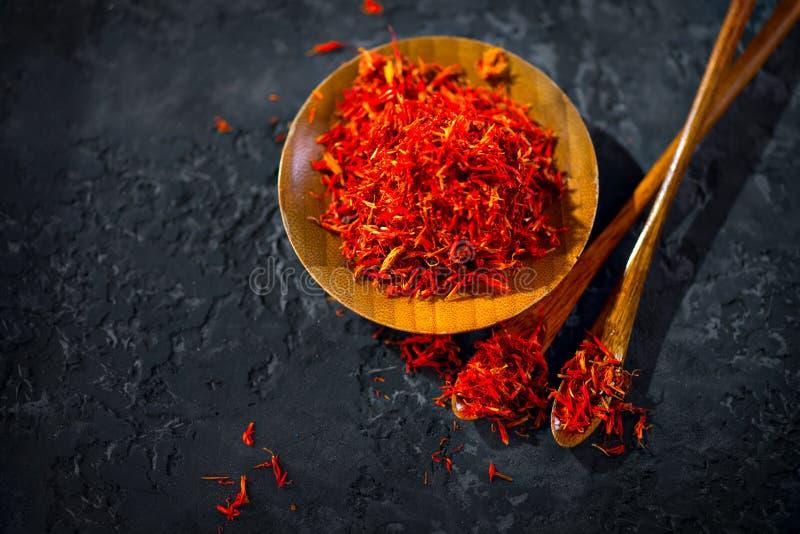 Saffron Spice Especiarias de Saffron em uma mesa de pedra preta em uma tigela de madeira e uma colher Especiarias e ervas aromáti fotos de stock