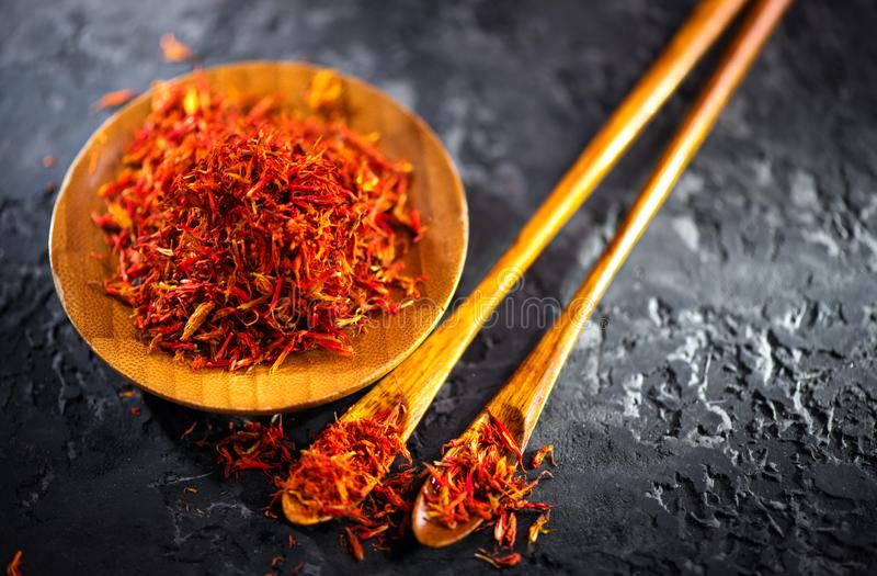 Saffron Spice. Saffron spices on black stone table in a wood bowl and a spoon. Spice and herbs on slate background. Seasonings. Condiments. Cooking ingredients stock photo