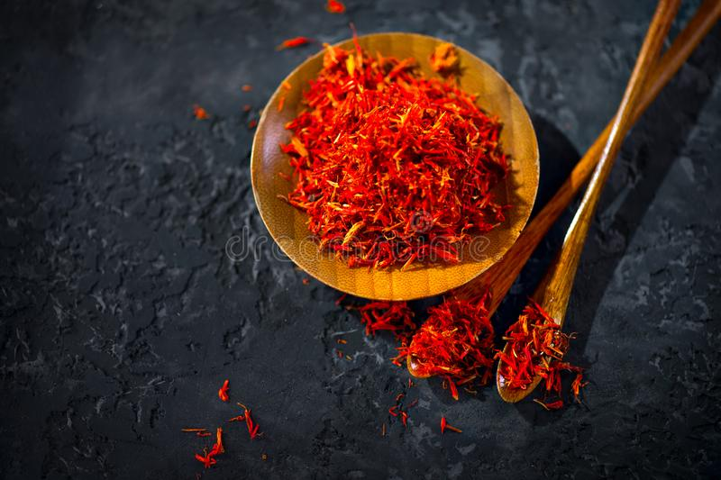 Saffron Spice. Saffron spices on black stone table in a wood bowl and a spoon. Spice and herbs on slate background. Seasonings. Condiments. Cooking ingredients stock photos