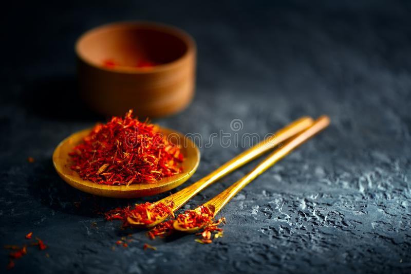 Saffron spices. Saffron on black stone table in a wood bowl and a spoon royalty free stock image