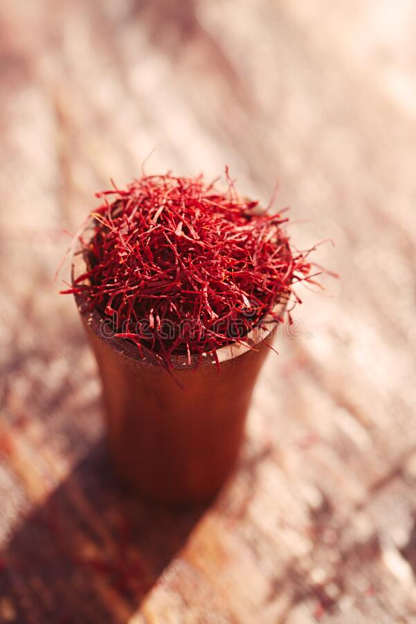 Saffron threads  pile in wooden cup with vintage wood backdrop stock images