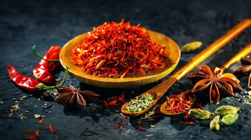 Saffron. Various Indian Spices on black stone table. Spice and herbs on slate background stock images