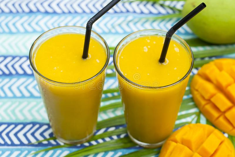 Saft av mango smoothie, färsk Blått textilmaterial Stäng arkivfoto