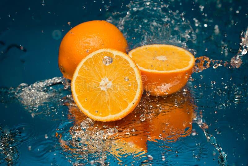 Saftig apelsin i sprej av vatten royaltyfri foto