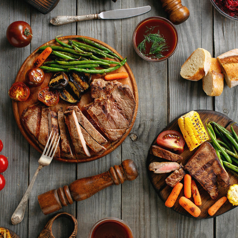 Saftig biff som lagas mat på ett galler med grillade grönsaker arkivbild