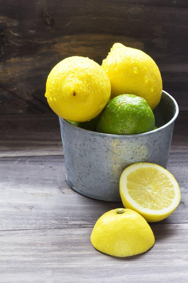 Saftig citrus på den lantliga trätabellen - limefrukt, citron och mintkaramell arkivfoto