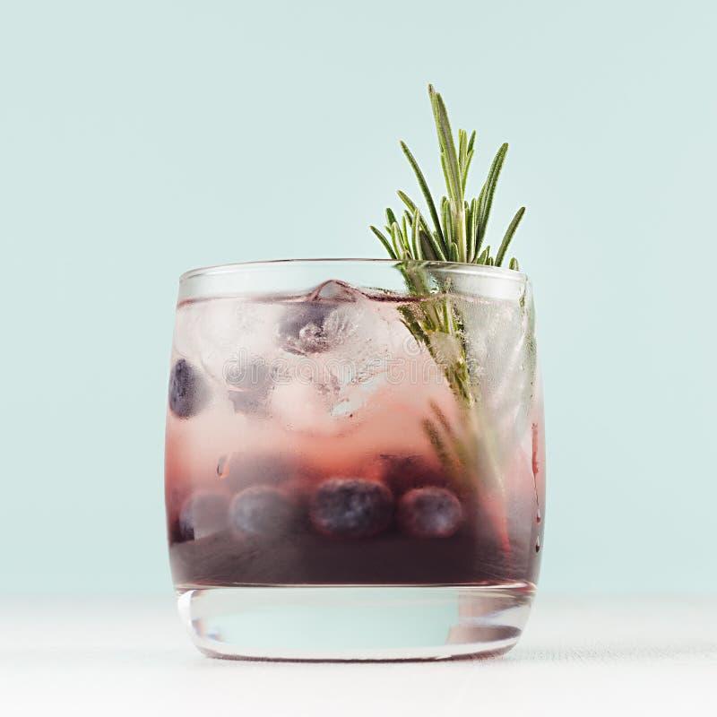Saftig coctail för ny sommar i exponeringsglas med iskuber, blåbär, rosmarin på den pastellfärgade mjuka tabellen för färg royaltyfri bild